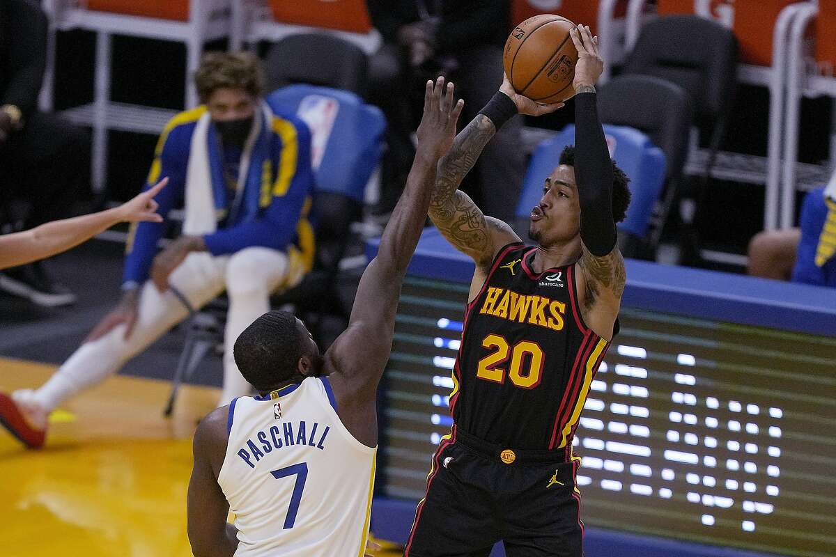 Hawks forward John Collins shoots over Golden State's Eric Paschall. A lot of teams have been shooting over the Warriors lately, often scoring more than 30 points per period.