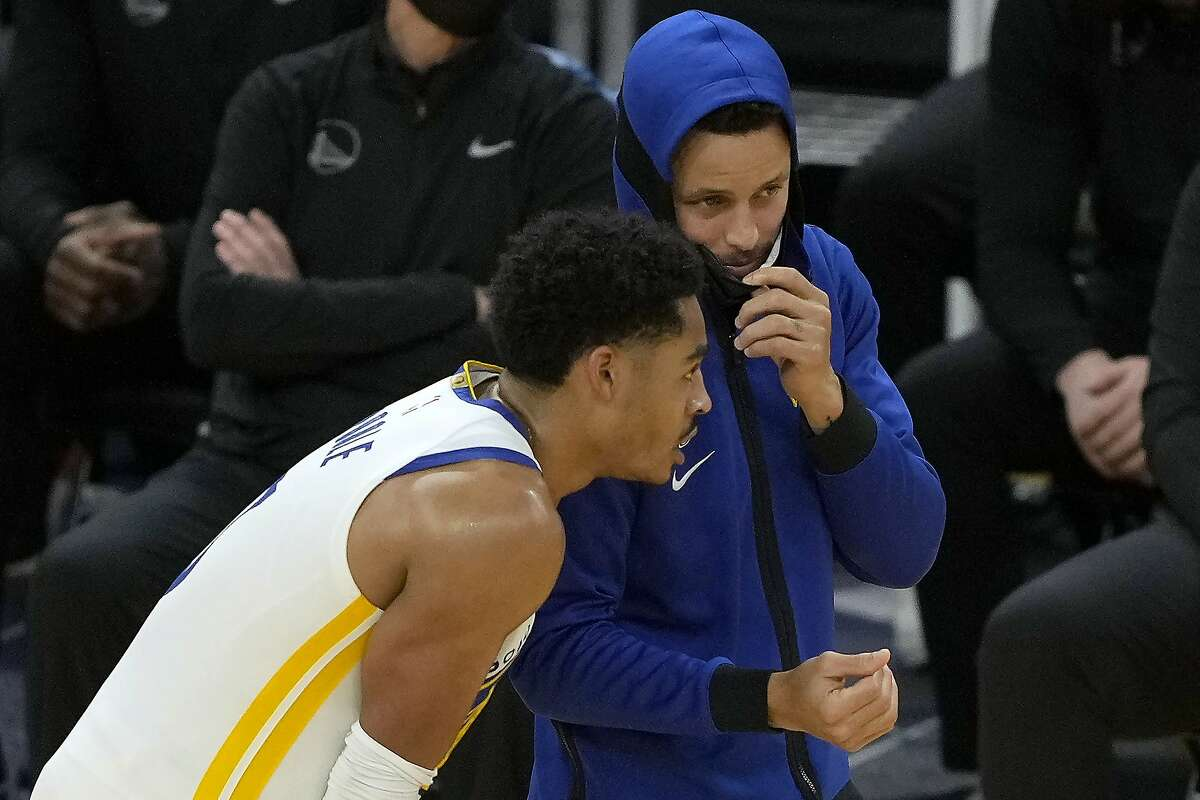 Golden State Warriors guard Stephen Curry, right, offers a pointer or two to Jordan Poole during the second half of Friday's game against the Atlanta Hawks.