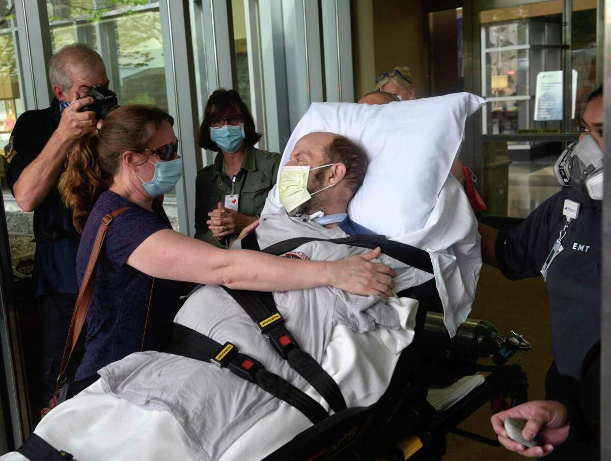 John Reed, deputy fire chief from New Rochelle, N.Y., gets a hug from his wife, Suzanne, after being discharged from Danbury Hospital May 29, 2020. Reed was in the hospital 56 days battling COVID-19.