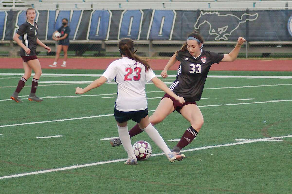 Dawson's Brooklyn Karr (23) and Clear Creek's Payton Hurst (33) fight for the ball Friday in a Class 6A soccer playoff at Friendswood High School.
