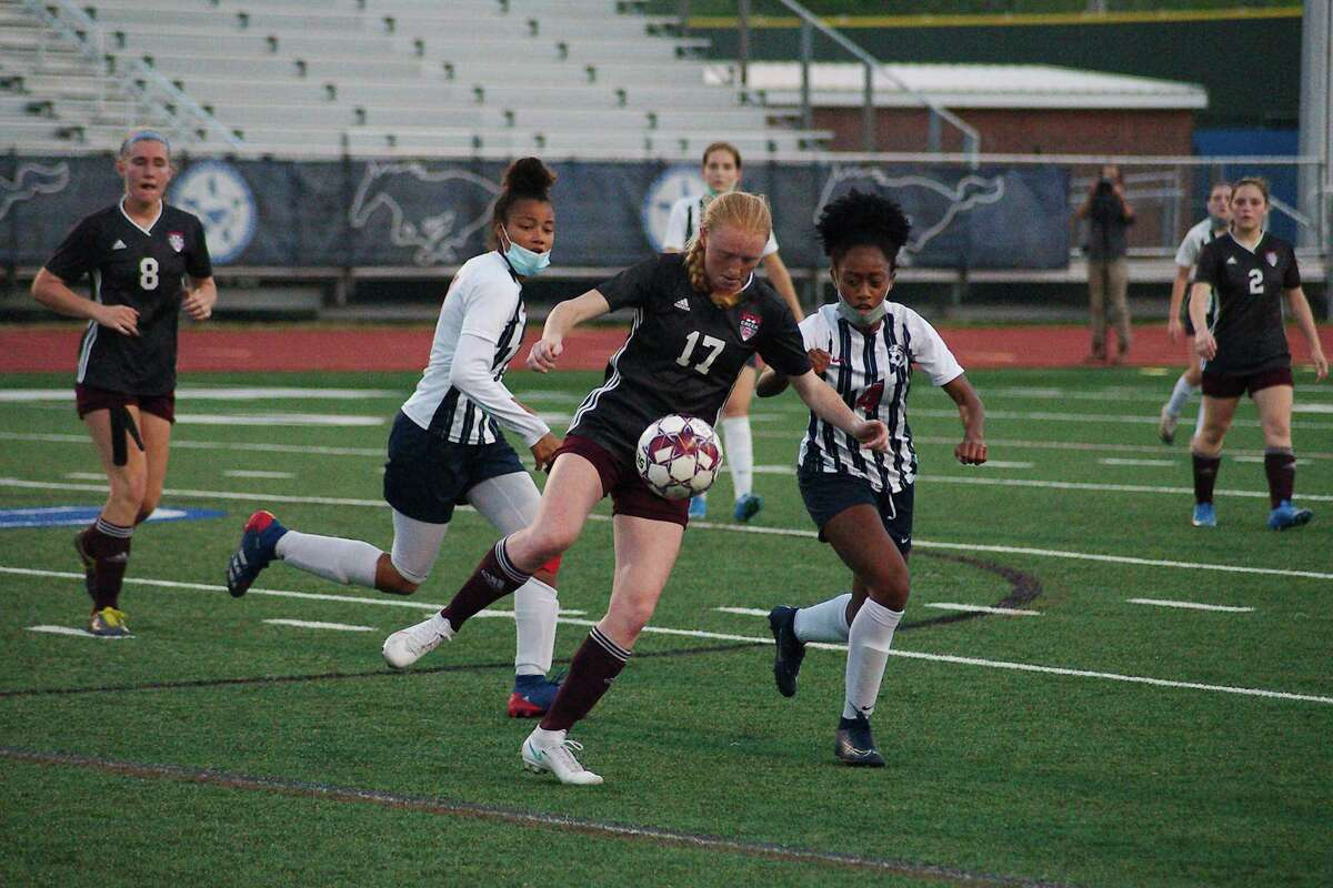 Clear Creek's Kasey Klages (17) tries to work the ball past Dawson's Gillian Powell (14) in a Class 6A soccer playoff at Friendswood High School.