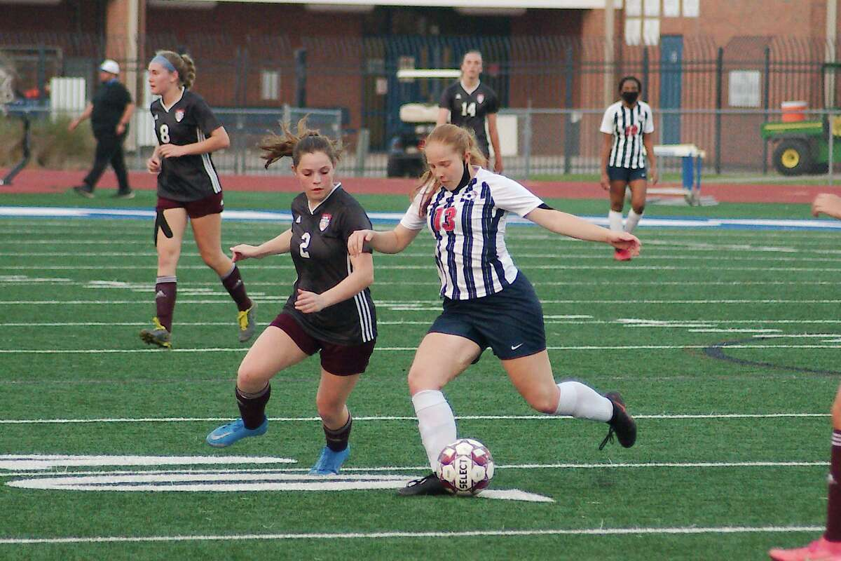 Dawson's Joanna Blake (13) protects the ball from Clear Creek's Helene Carney (2) Friday in a Class 6A soccer playoff at Friendswood High School.