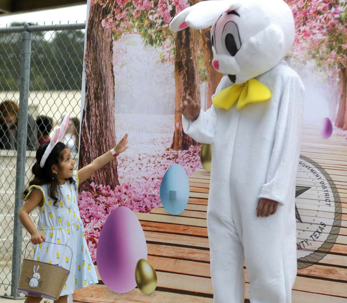 Wendy Carrillo waves to the Easter Bunny at East Montgomery County Improvement District's Eggcellent Event and Spring Mini-Market at New Caney Middle School, Saturday, March 27, 2021, in New Caney. Children were also able to take part in an Easter egg hunt with 80,000 brightly colored eggs scattered across Don Ford Stadium.
