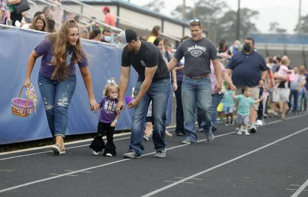 Parents and children make their way to the field to take part in an egg hunt during East Montgomery County Improvement District's Eggcellent Event and Spring Mini-Market at New Caney Middle School, Saturday, March 27, 2021, in New Caney. Photo: Jason Fochtman/Staff Photographer / 2021 ? Houston Chronicle