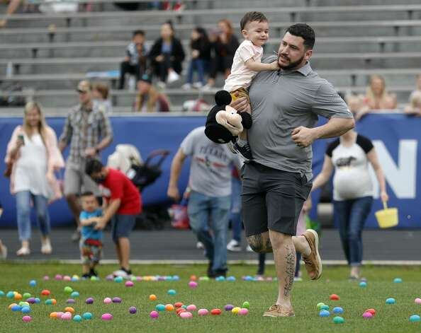 Jose Rivas carries his son Mateo to a large group of clustered Easter eggs during East Montgomery County Improvement District's Eggcellent Event and Spring Mini-Market at New Caney Middle School, Saturday, March 27, 2021, in New Caney. Children were also able to take part in an Easter egg hunt with 80,000 brightly colored eggs scattered across Don Ford Stadium. Photo: Jason Fochtman/Staff Photographer / 2021 ? Houston Chronicle