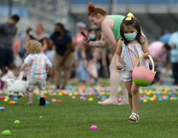 A girl wears a face mask as she picks up colorful eggs during East Montgomery County Improvement District's Eggcellent Event and Spring Mini-Market at New Caney Middle School, Saturday, March 27, 2021, in New Caney. Children were also able to take part in an Easter egg hunt with 80,000 brightly colored eggs scattered across Don Ford Stadium. Photo: Jason Fochtman/Staff Photographer / 2021 © Houston Chronicle