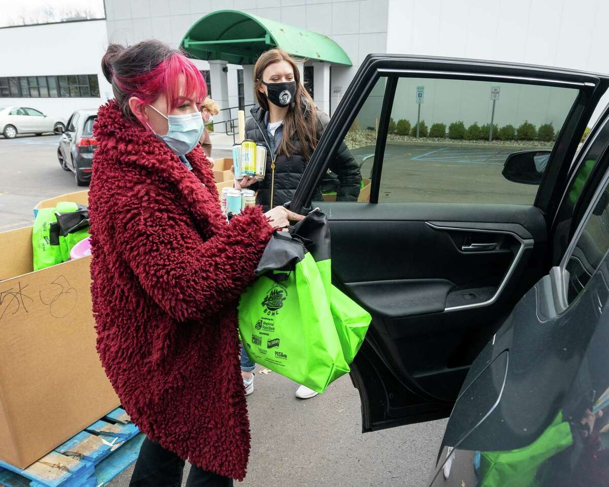 Bella Episcopo (left) and Josie Corbett load up a car with a take-out bag full of mac-n-cheese and a rack of beverages during the 11th Annual Times Union Table Hopping Mac-n-Cheese Bowl to benefit the Regional Food Bank of Northeastern New York. The sold out event was to-go style because of COVID and there were a steady stream of cars driving through the food bank's parking lot on Albany Shaker Road on Saturday, March 27, 2021. (Jim Franco/Special to the Times Union)