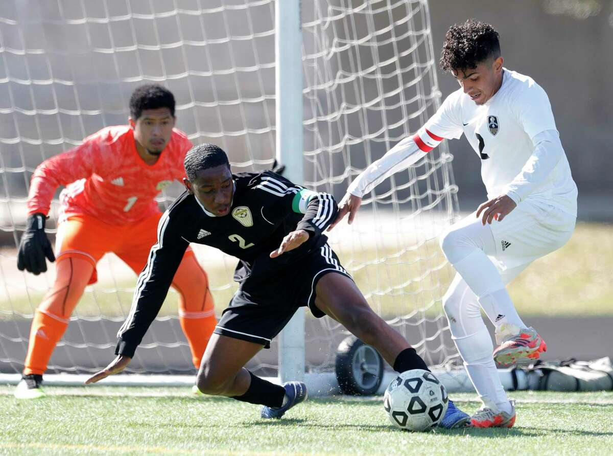 Conroe's Carlos Salinas (2) works the ball against Sharpstown's Jostin Garcia Lagos (2) as goalie Joalmo Cavezas (1) looks on in the first period of a match during the Kilt Cup soccer tournament, Saturday, Jan. 9, 2021, in Conroe. Conroe defeated Sharpstown 4-3.