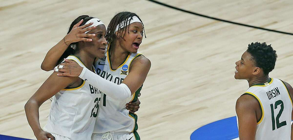 Baylor forward NaLyssa Smith (1) hugs Baylor center Queen Egbo (25) as Baylor guard Moon Ursin (12) comes into the celebration after Baylor defeated Michigan 78-75 in OT on Saturday, March 27, 2021 at the Alamodome.