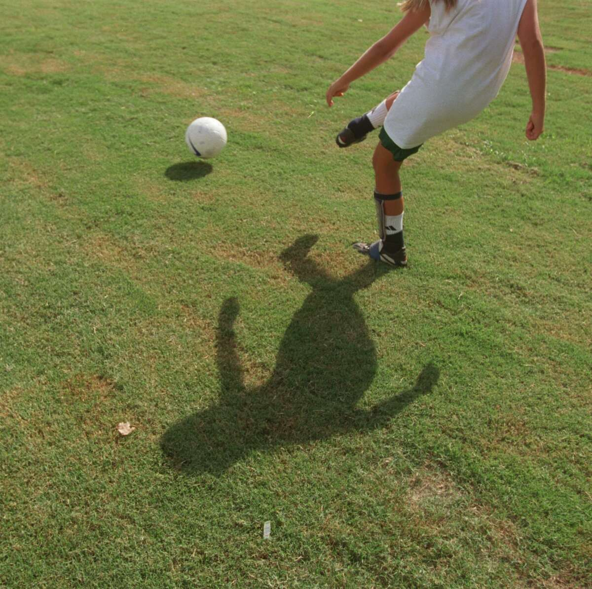 (8/26/99) With the sun beating down, and casting a long, hot shadow, Mary Elizabeth Donovan, 11, kicks a soccer ball during practice to her teammate, Carolyn Cohen, 11, Thursday afternoon at a West University soccer field. The girls are on the West U Express, under 12 soccer team. (Karen Warren/Houston Chronicle) HOUCHRON CAPTION (08/27/1999): Practice, practice, practice. Mary Elizabeth Donovan, 11, kicks the ball to a teammate as the West U Express girls soccer team practices Thursday afternoon. The girls, all under 12 years old, took advantage of the weather to go over plays at a soccer field in West University Place.