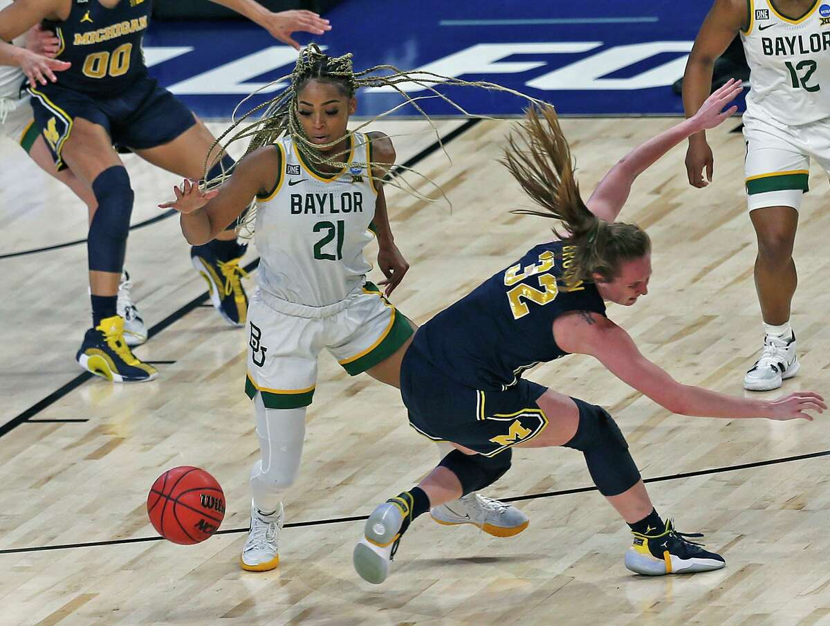 Baylor guard Dijonai Carrington (21) steals the ball from Michigan guard Leigha Brown (32) in the first half on Saturday, March 27, 2021 at the Alamodome.