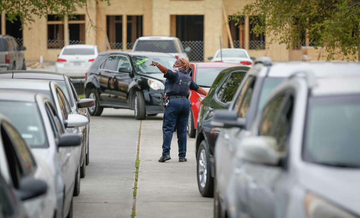 Harris County Sheriff Deputy, Lisa Reece directs traffic during a rent assistance through the joint Houston-Harris County Emergency Rental Assistance Program and the Texas Rent Relief Program at the Greenspoint Harvest Time Church Saturday, March 27, 2021, in Houston.