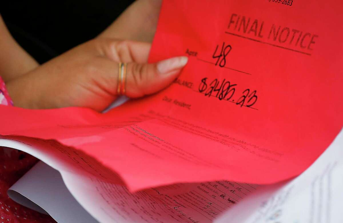 A tenant shows her final notice with the amount of $2,495.23 due durning a rent assistance event through the joint Houston-Harris County Emergency Rental Assistance Program and the Texas Rent Relief Program at the Greenspoint Harvest Time Church Saturday, March 27, 2021, in Houston.