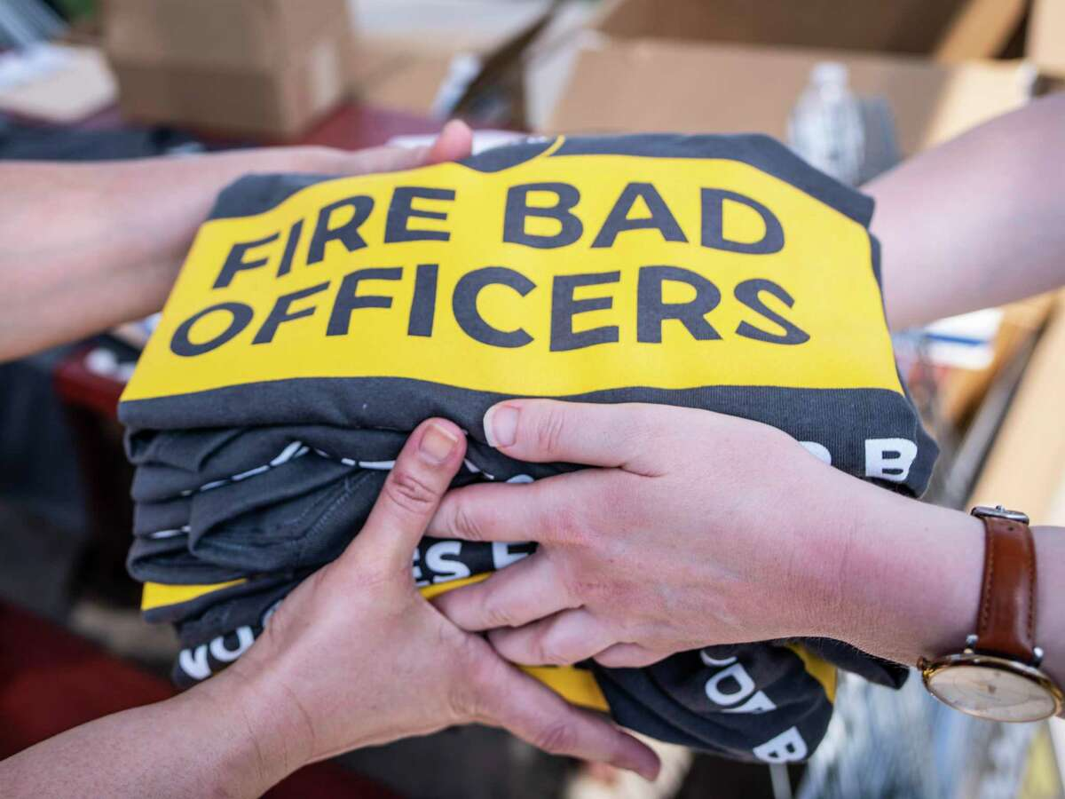 """T-shirts bearing the phrase, """"Fire Bad Officers,"""" are sold during a rally to support Proposition B, which would repeal the San Antonio police union's ability to collectively bargain. The rally was held at Pittman-Sullivan Park on Saturday."""