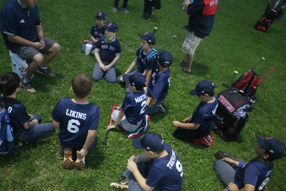 Members of the NASA Area Little League Red Sox listen to their manager following their season opener this past Wednesday night at Steve Alves Field.
