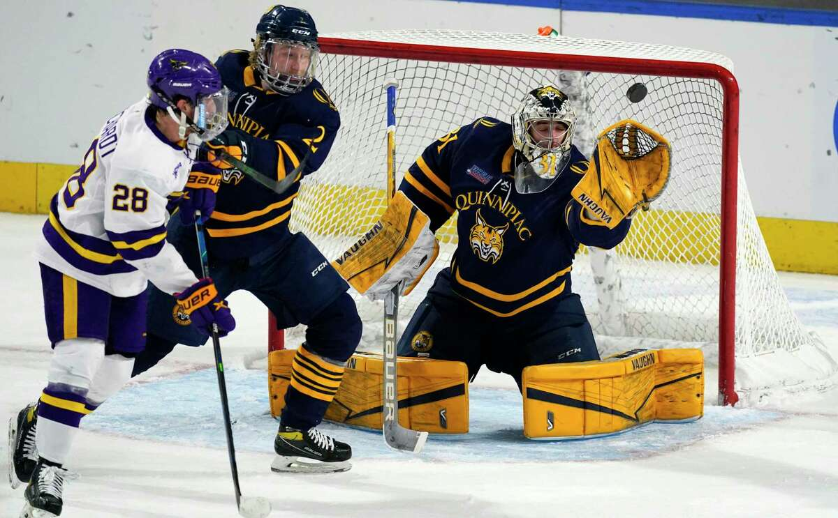 Quinnipiac goaltender Keith Petruzzelli, right, makes a glove save as defenseman Iivari Rasanen, center, jostles for position in front of the net with Minnesota State forward Cade Borchardt during the second period on Saturday.