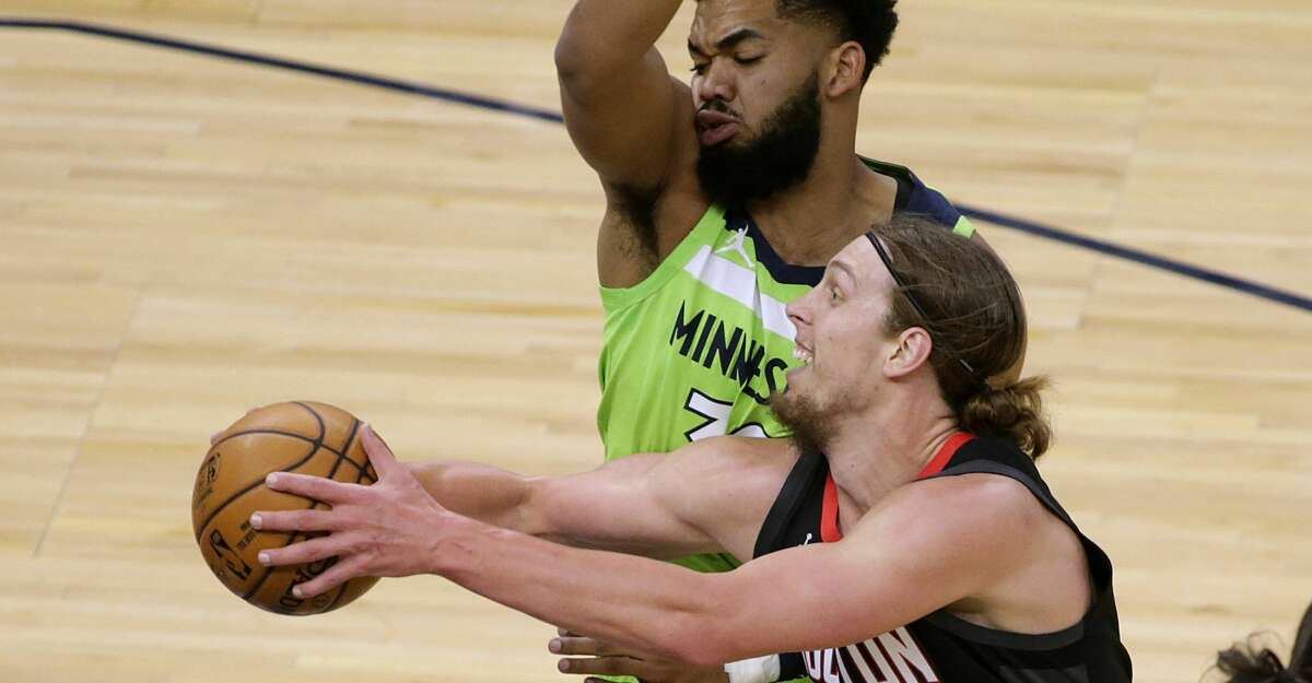 Houston Rockets center Kelly Olynyk (41) drives on Minnesota Timberwolves center Karl-Anthony Towns (32) during the first quarter of an NBA basketball game Saturday, March 27, 2021, in Minneapolis. (AP Photo/Andy Clayton-King)