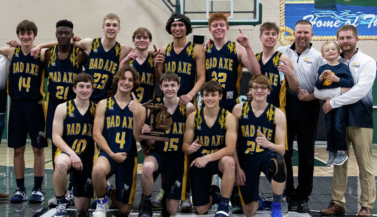 The Bad Axe boys varsity basketball team poses with its district championship trophy following its 67-62 victory over Harbor Beach at Laker High School on Saturday night. The Hatchets will meet up with the Reese Rockets in the regional semifinals on Tuesday night. at Reese High School.