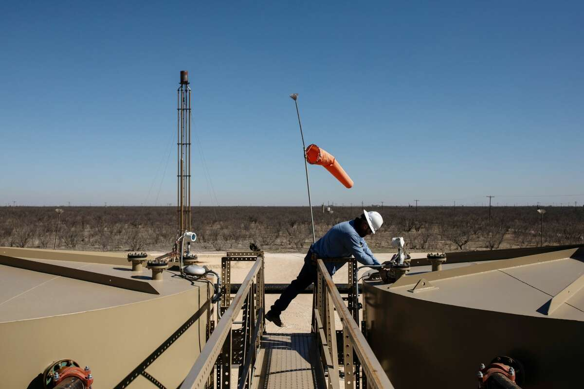 A field technician gauges a production tank east of Midland in this 2019 file photo. The Dallas Fed's most recent energy survey found activity expanded strongly in the first quarter.