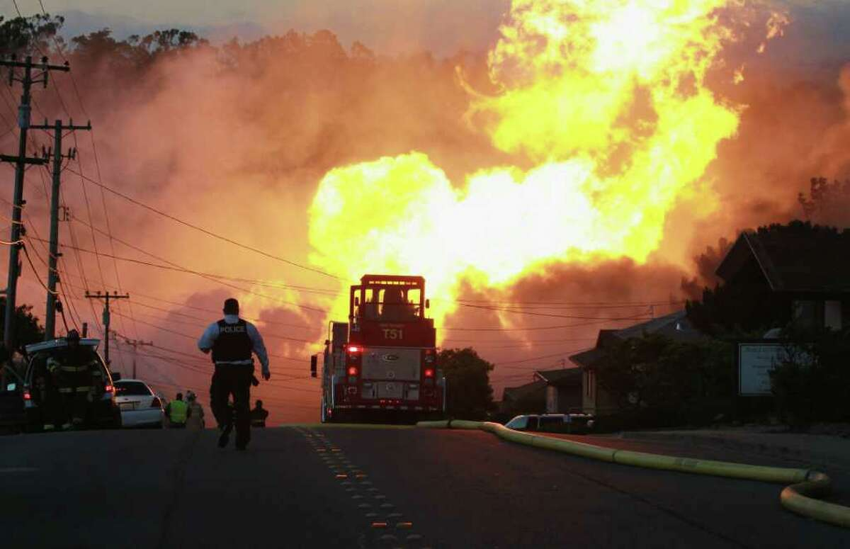 SAN BRUNO, CA - SEPTEMBER 09: A law enforcement official runs towards a massive fire in a residential neighborhood September 9, 2010 in San Bruno, California. A massive explosion rocked a neighborhood near San Francisco International Airport. (Photo by Justin Sullivan/Getty Images)