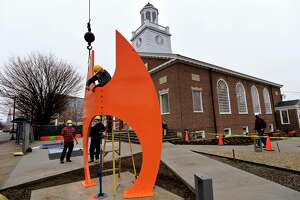 Studio emplyees of artist Gilbert Boro install a 16-foot steel sculpture, ATR (After The Race) in the front sculpture garden of the new Norwalk Art Space Friday, March 26, 2021, in Norwalk, Conn. The free arts hub is also hosting a meet and greet Saturday with its resident artists, fellows and team members as they prepare to open in the coming months.