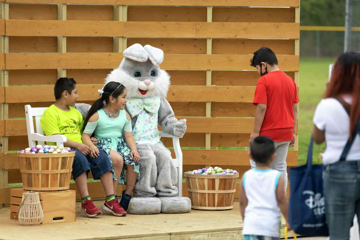 Mr. Bunny poses for portraits with children during an Easter egg hunt hosted by the City of Conroe Parks & Recreation department at Carl Barton Park on Saturday in Conroe..