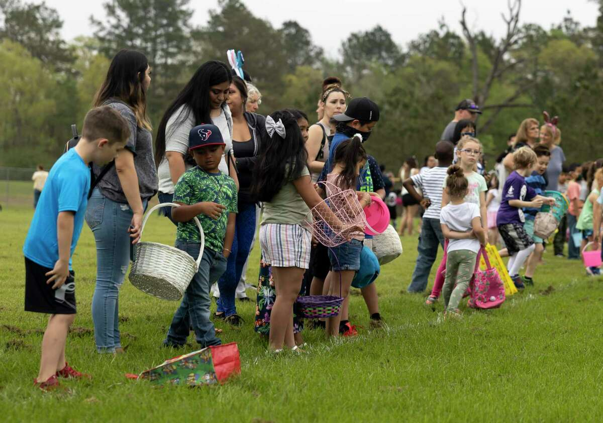 Children and guardians lineup in preparation of an Easter egg hunt hosted by the City of Conroe Parks & Recreation department at Carl Barton Park, Saturday, March 27, 2021, in Conroe. Over 20,000 eggs were spread throughout four softball fields for kids to grab.