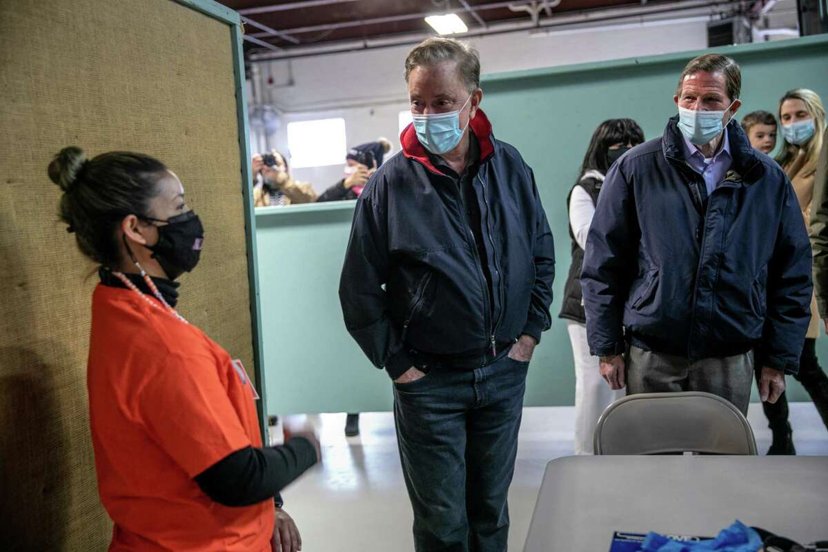 STAMFORD, CONNECTICUT - MARCH 14: CT Governor Ned Lamont (D-CT) (C), and Senator Richard Blumenthal (D-CT) (R), speak with a volunteer at a community vaccination clinic on March 14, 2021 in Stamford, Connecticut. The non-profit Building One Community organized the event to administer the first dose of the Moderna vaccine to more than 350 people from the immigrant and undocumented communities. The vaccines were supplied by the federal Health Resources and Services Administration (HRSA). Vaccine recipients are due to return in April for their second dose. (Photo by John Moore/Getty Images)