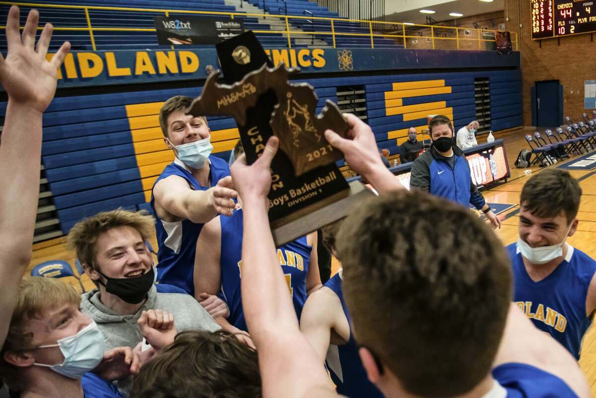 Midland players hoist their trophy after the Chemics' district final victory over Mount Pleasant Saturday, March 27, 2021 at Midland High School. (Isaac Ritchey/for the Daily News)