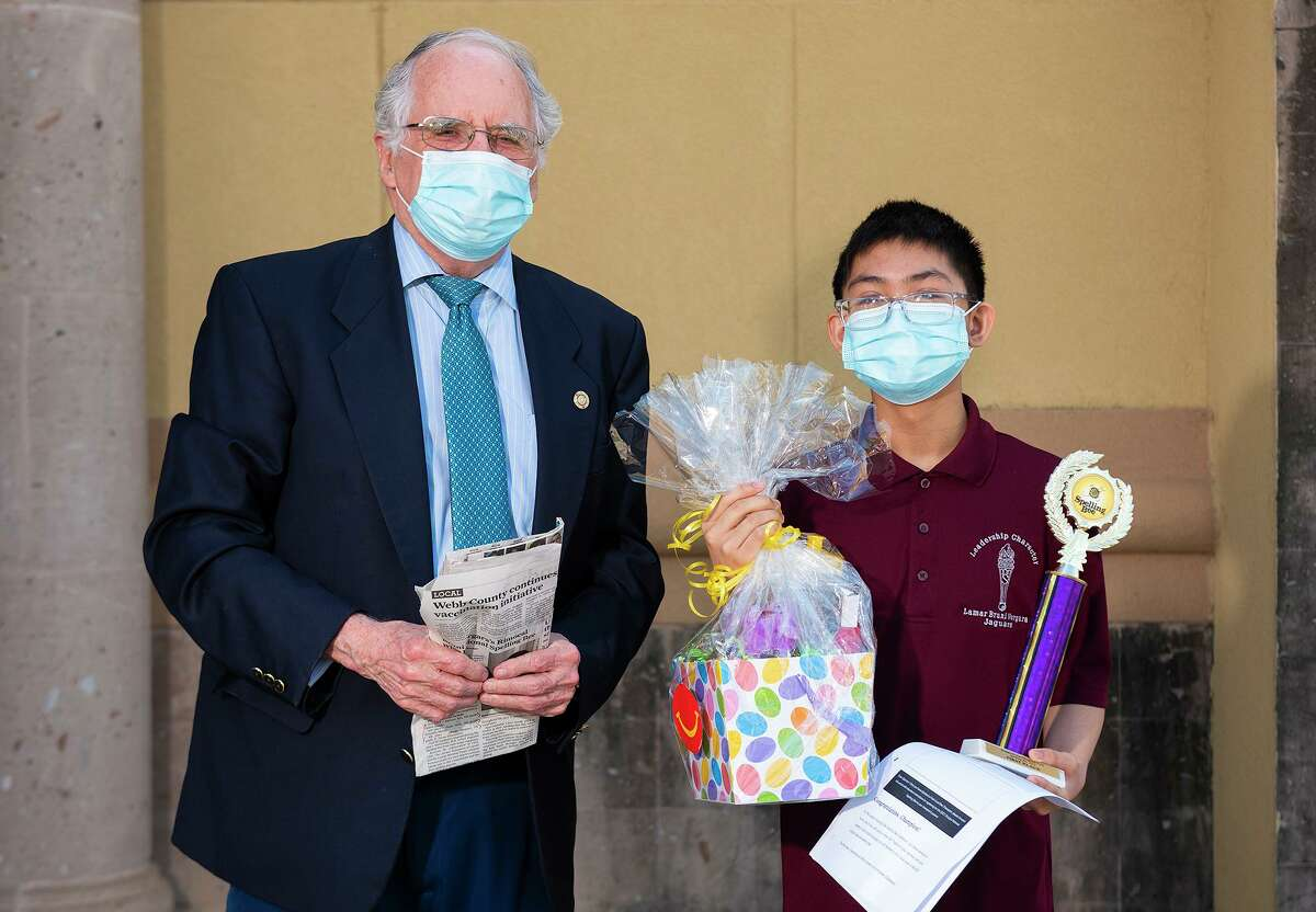 Laredo Morning Times Publisher Bill Green presents Lamar Bruni Vergara Middle School eighth grader Emmanuel Rimocal with his first-place trophy from the regional spelling bee in this March 27, 2021 photo.