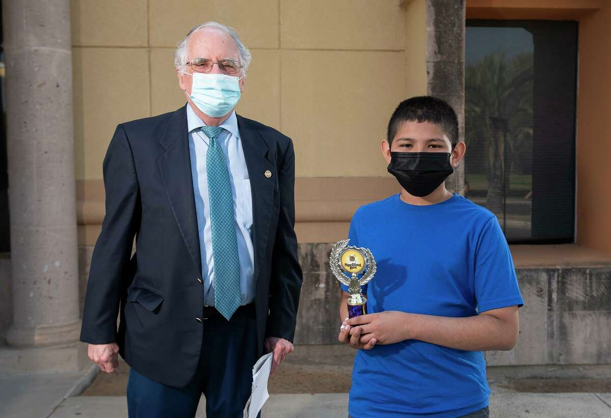 Laredo Morning Times Publisher Bill Green presents Tarver Elementary 5th grader Alfredo Vasquez with his fourth-place trophy Saturday, March 27, 2021 outside Laredo Morning Times.