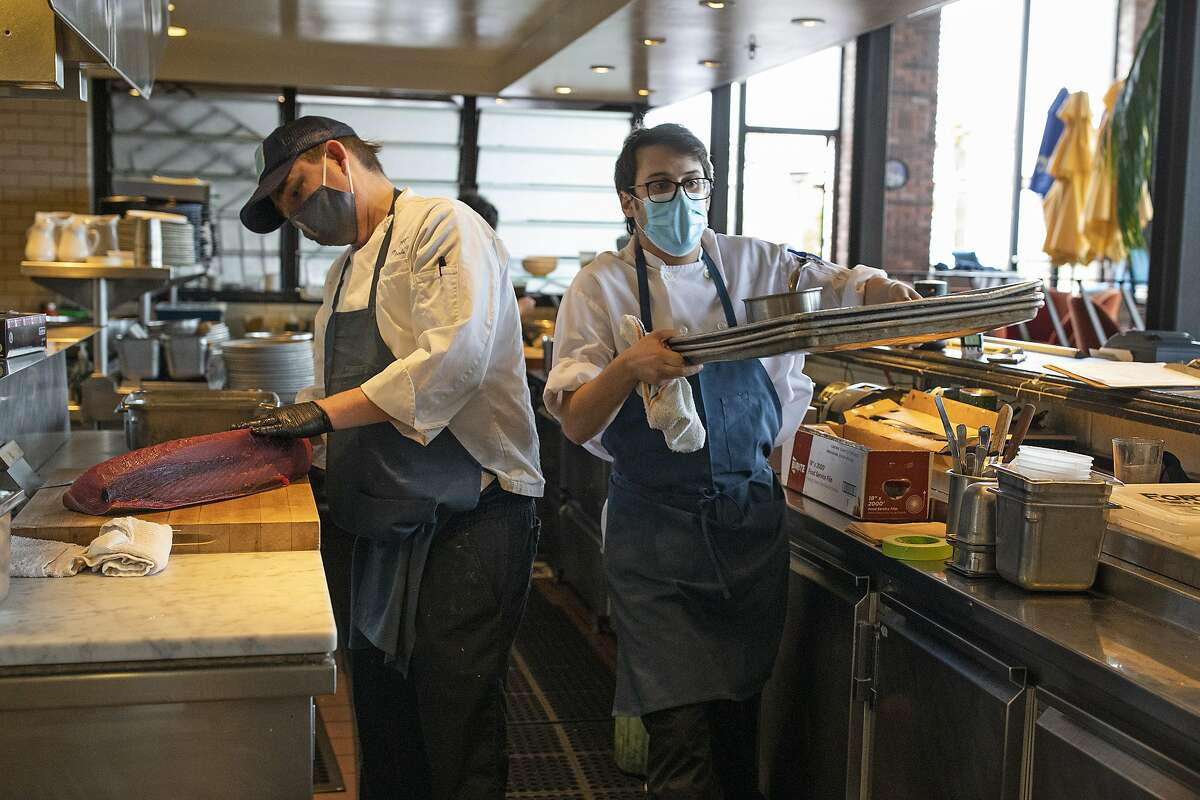 New state figures for February show improvement month-over-month in seven of California's 11 job sectors, including leisure and hospitality particularly in full-service restaurants. From left, Chef de Cuisine Justin Baade and cook Zach Langille inside Waterbar's kitchen, Tuesday, March 2, 2021, in San Francisco, Calif.