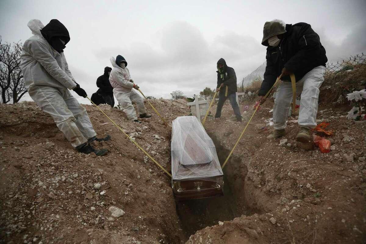 ARCHIVO - En esta imagen del 27 de octubre de 2020, trabajadores con equipos de protección colocan un ataúd en una tumba en una zona del cementerio municipal de San Rafael para personas fallecidas por COVID-19, en Ciudad Juárez, México. (AP Foto/Christian Chavez, Archivo)