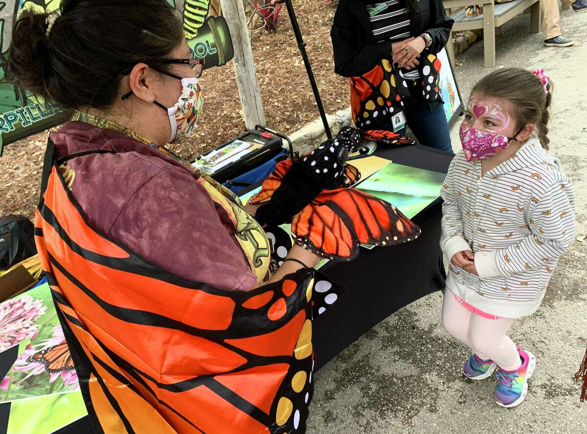 San Antonio Zoo butterfly attendant Roxanne Jacobsen demonstrates the transformation of a monarch butterfly to Charlotte Ponthier, 6½, at the zoo's Monarch Fest on Sunday.