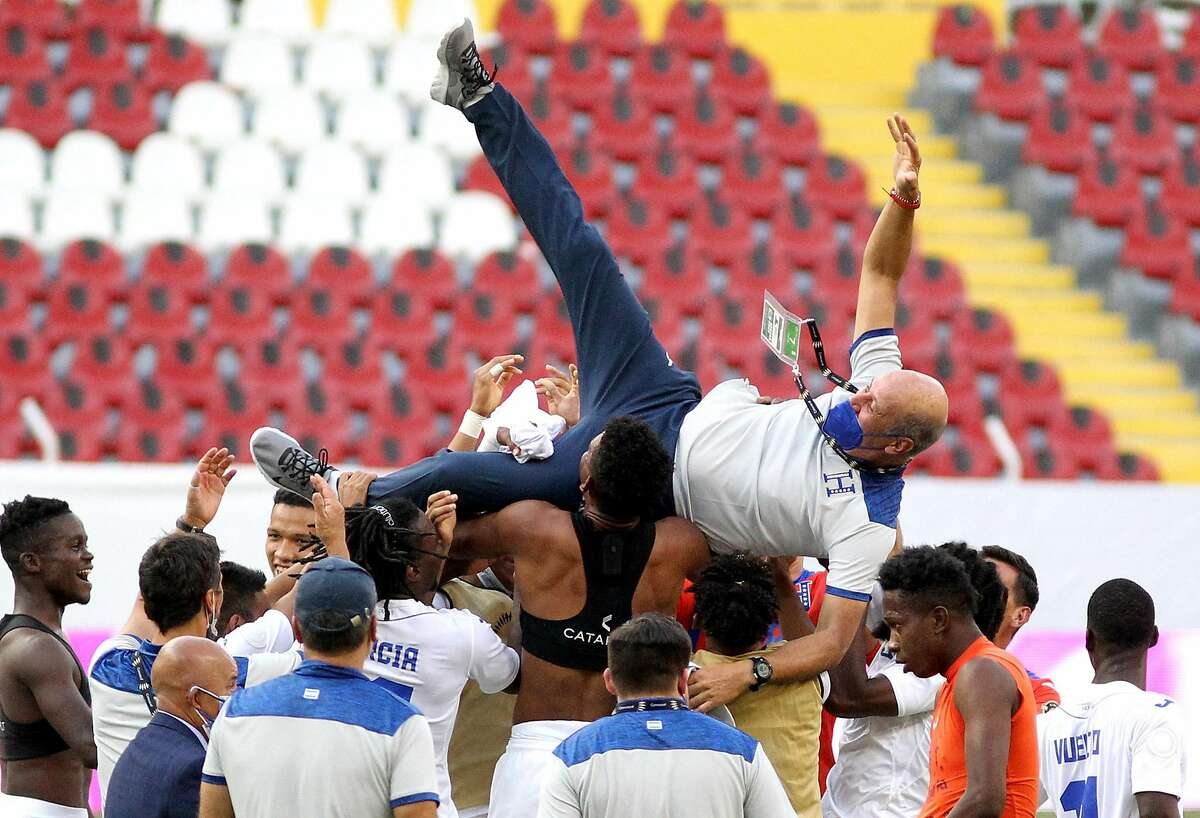 Honduras players lift coach Miguel Falero as they celebrate making the Tokyo Olympics - at the expense of the U.S.