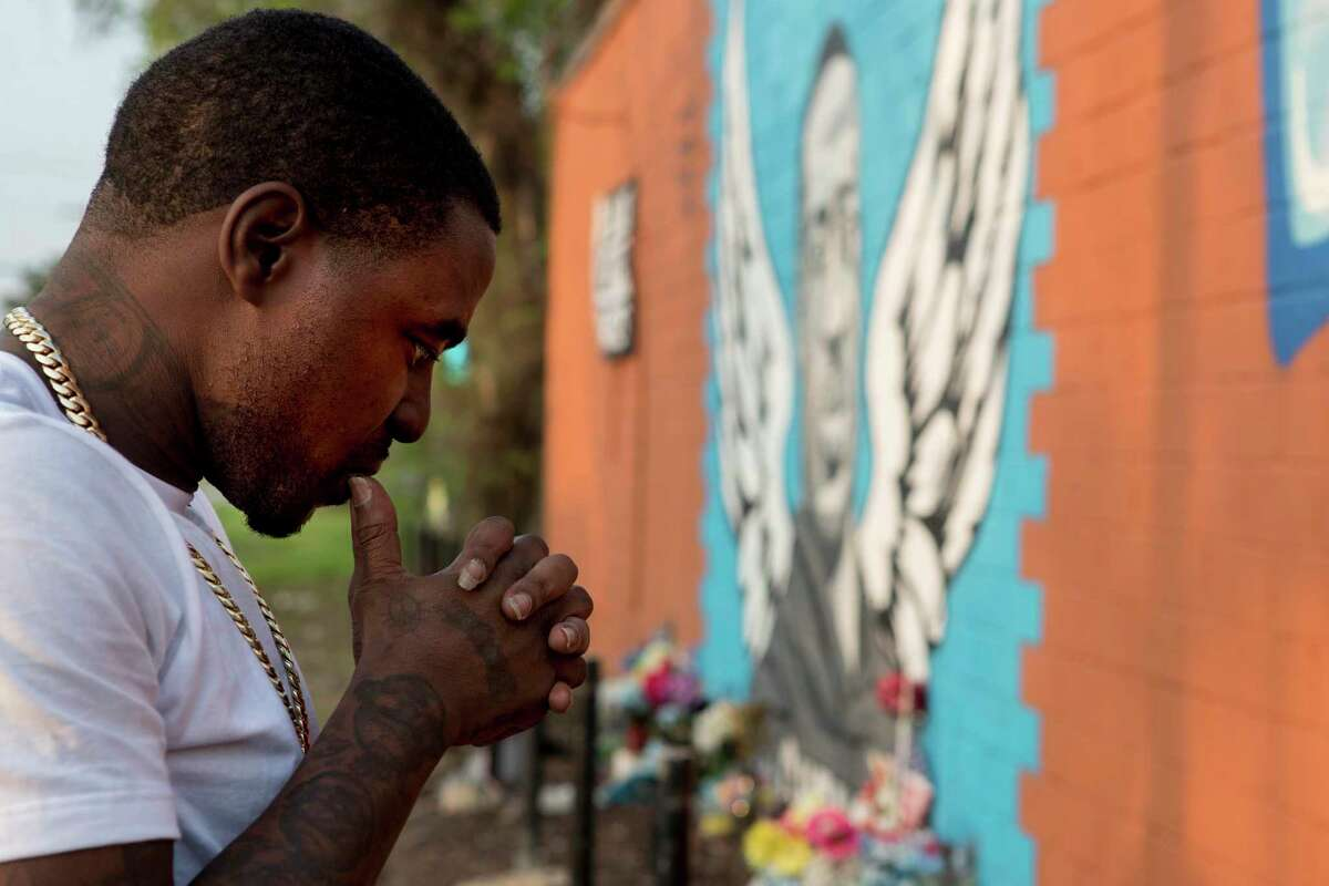 Rap artist Cal Wayne pauses at the George Floyd memorial mural in 3rd Ward Friday, March 26, 2021 in Houston. Wayne said he expects to be in Minneapolis for the trial of former Minneapolis police officer Derek Chauvin, who was charged with murder in Floyd's death. for up to five days to show his support.