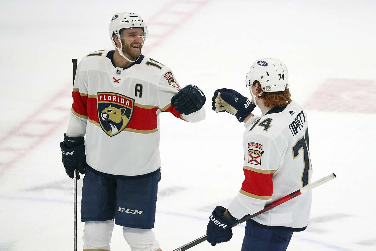 Florida Panthers left wing Jonathan Huberdeau (11) celebrates a third period goal by right wing Owen Tippett (74) against the Dallas Stars during an NHL hockey game on Sunday, March 28, 2021, in Dallas. (AP Photo/Richard W. Rodriguez)