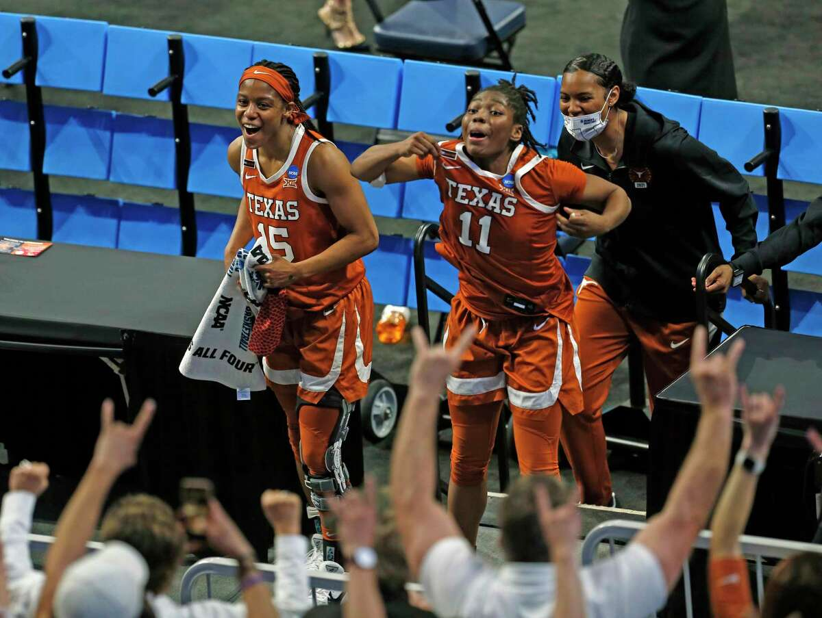 Texas guard Kyra Lambert (15) and Texas guard Joanne Allen-Taylor (11) celebrate with fans on Sunday, March 28, 2021 at the Alamodome. Texas defeated Maryland 64-61