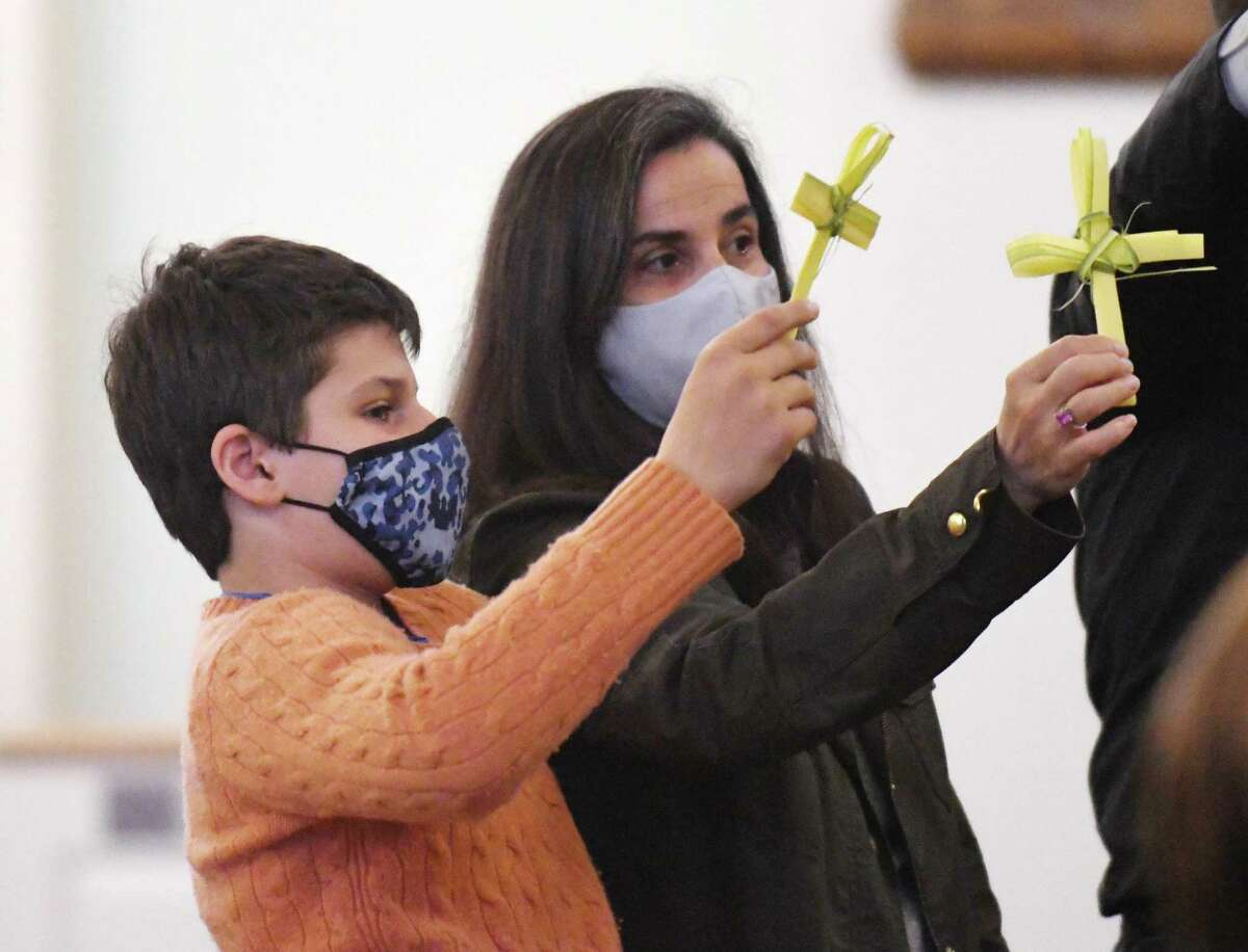 Cos Cob's Chrystele Zawislack and Anthony Zawislack, 12, hold their palm fronds during the Palm Sunday service at St. Catherine of Siena in the Riverside section of Greenwich, Conn. Sunday, March 28, 2021. Palm Sunday is the Christian holiday that commemorates Jesus's entry into Jerusalem and the start of Holy Week. Palm fronds are often distributed during the service to symbolize the palm branches that the crowd scattered in front of Christ as he rode into Jerusalem. Cos Cob's Chrystele Zawislack and Anthony Zawislack, 12, were among those who held palm fronds as the Rev. Bill Platt celebrated Mass on Sunday. The faithful will march Holy Week in the coming days, with Easter on Sunday, April 4.