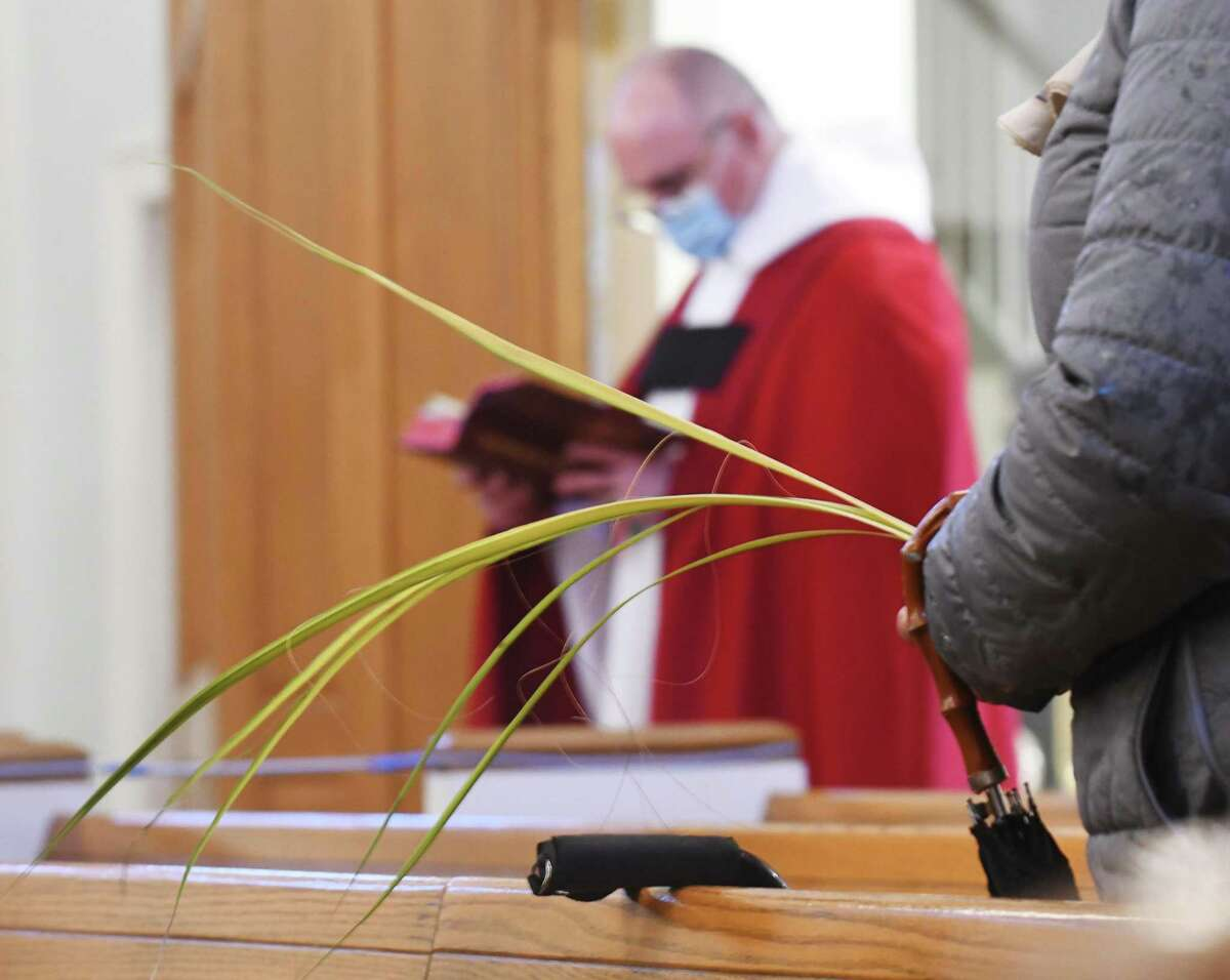 A congregant holds palm fronds during the Palm Sunday service at St. Catherine of Siena in the Riverside section of Greenwich, Conn. Sunday, March 28, 2021. Palm Sunday is the Christian holiday that commemorates Jesus' entry into Jerusalem and the start of Holy Week. Palm fronds are often distributed during service to symbolize the palm branches that the crowd scattered in front of Christ as he rode into Jerusalem.