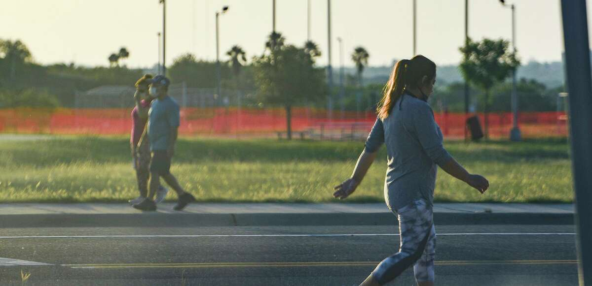 Walkers wear masks as they exercise along the Merida Drive sidewalk on Friday, April 24, 2020.