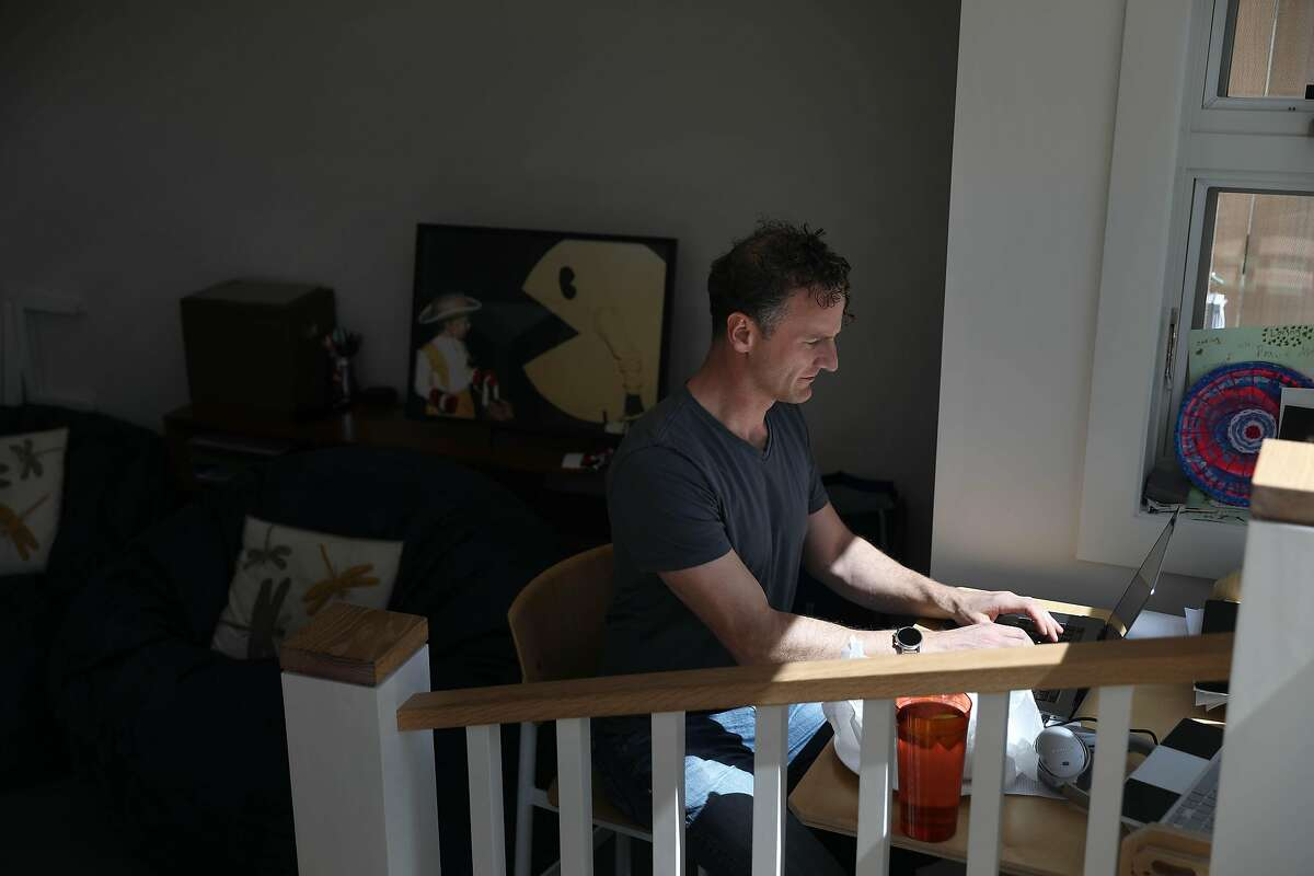 Rob Cocks, of San Francisco, works from home in his home office on Friday, March 26, in San Francisco, Calif. Cocks is currently unvaccinated and surrounded by folks who are vaccinated - first went his in-laws and his parents and now his wife has had her first dose.