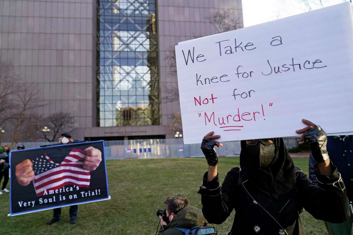 Demonstrators hold signs during a news conference outside the Hennepin County Government Center, Monday, March 29, 2021, in Minneapolis where the trial for former Minneapolis police officer Derek Chauvin began with opening statements from both sides. Chauvin is charged with murder in the death of George Floyd during an arrest last May in Minneapolis.