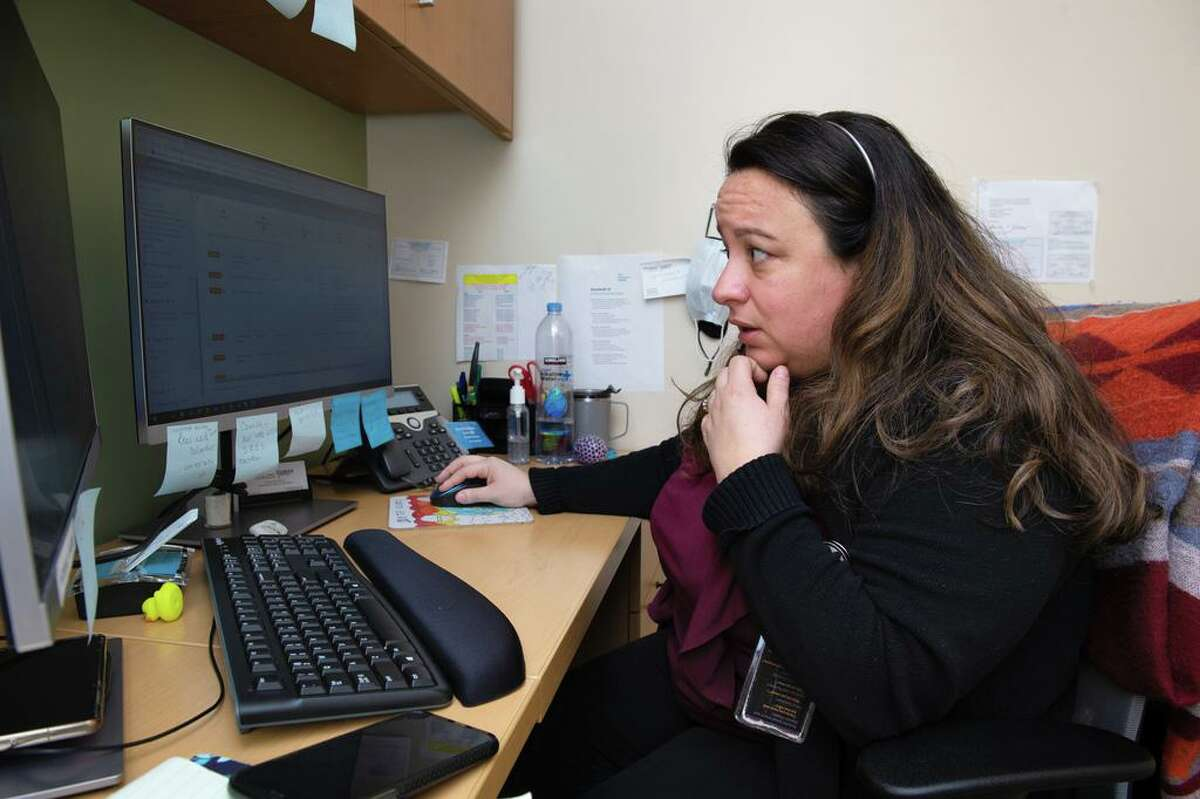 Katia Astudillo, a Community Health Worker at Project Access New Haven, talks on the phone to a client with health issues to follow up on connecting her to community resources, March 18, 2021.