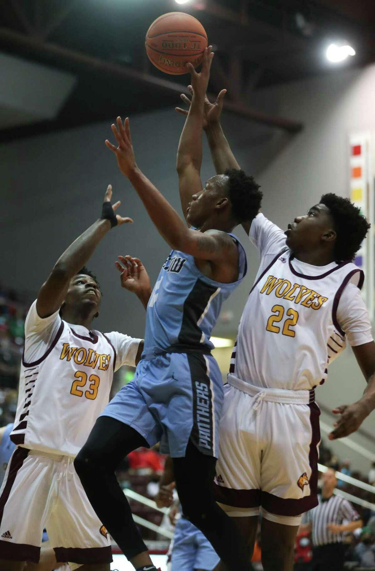 Katy Paetow guard Trevor Frank goes up for a shot between Beaumont United's Terrance Arceneaux (23) and Clarence Payia (22) during the first half of the boys Class 5A Region III championship basketball game at the Campbell Center Friday, March 5, 2021 in Houston.