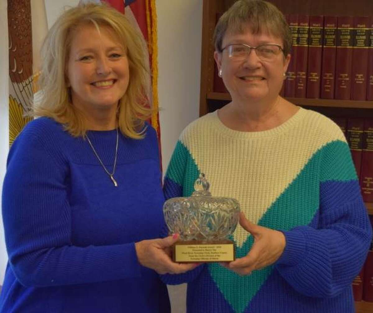 Wood River Township Clerk Sherry Tite, left, receives the 2020 William Z. Ahrends Award from Cass Township Clerk Jeanette McWhorter.