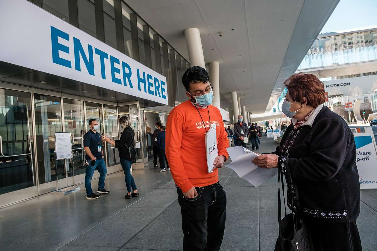 A greeter is seen helping people navigate the entrance to the mass vaccination site at the Moscone Center in San Francisco. Health experts urge the public to cancel unneeded appointments to not let doses go to waste.