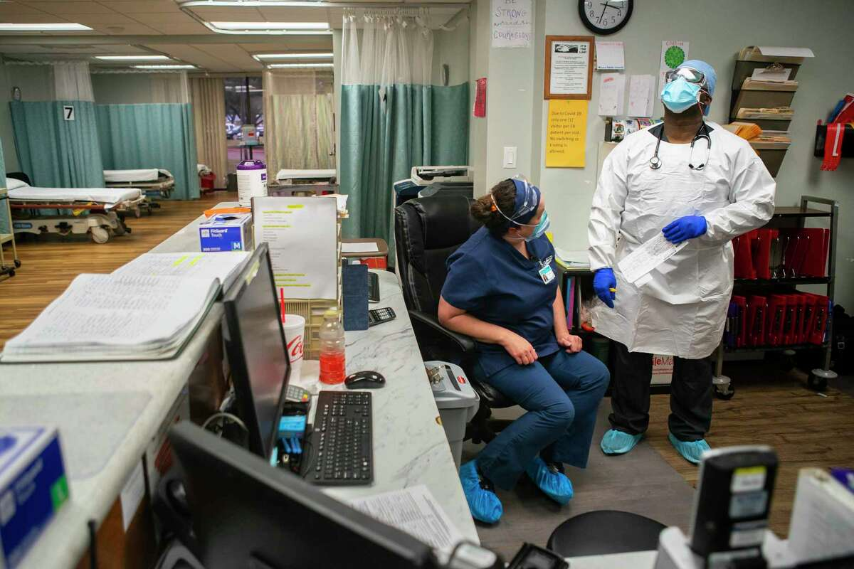 Nurse Tanya Metz talks with Dr. Gabriel Agbanyim about a COVID patient that is being brought to the ICU from the emergency room, Monday, July 20, 2020, at El Campo Memorial Hospital in El Campo, TX.
