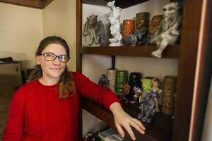 Cindy Trombley poses for a portrait alongside several of the gargoyles included in her collection, Tuesday, Feb. 16, 2021 at her home in Midland. (Katy Kildee/kkildee@mdn.net)