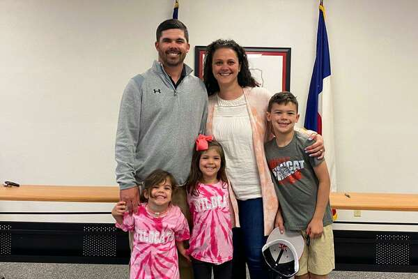 Trey Allen, the new football coach and athletic director at Kirbyville, poses for a picture Monday with his wife Meggan and their three children.